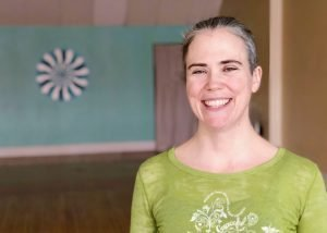 Headshot of Elle Newman wearing green yoga shirt and smiling broadly.
