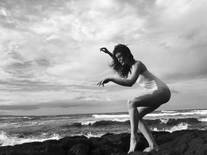 Black and White photo of woman dancing on edge of ocean