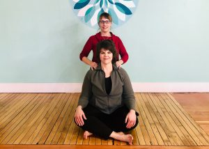 2 smiling yoga teachers named April and Alanna. Alanna is giving April a shoulder massage.