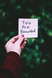 "woman's hand holding note that says, ""You Are Beautiful"""