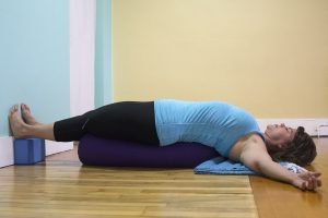 Full bodied female yoga teacher lying in a restorative pose. She looks very comfortable and the feeling of the photo is very inviting.