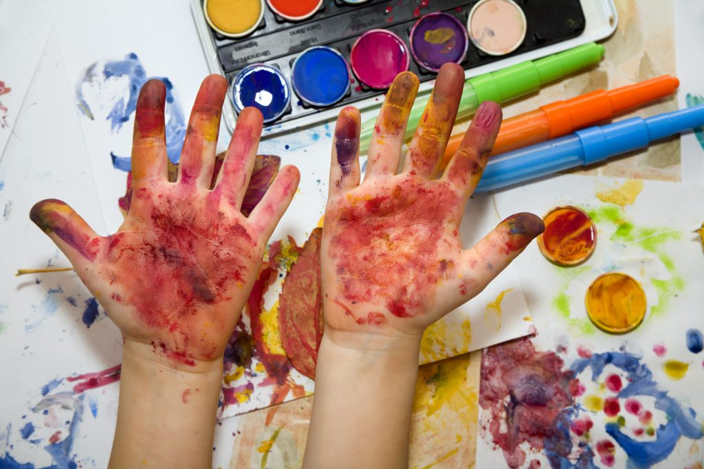 Hands covered with paint, a set of watercolors in the background. Creativity is messy.