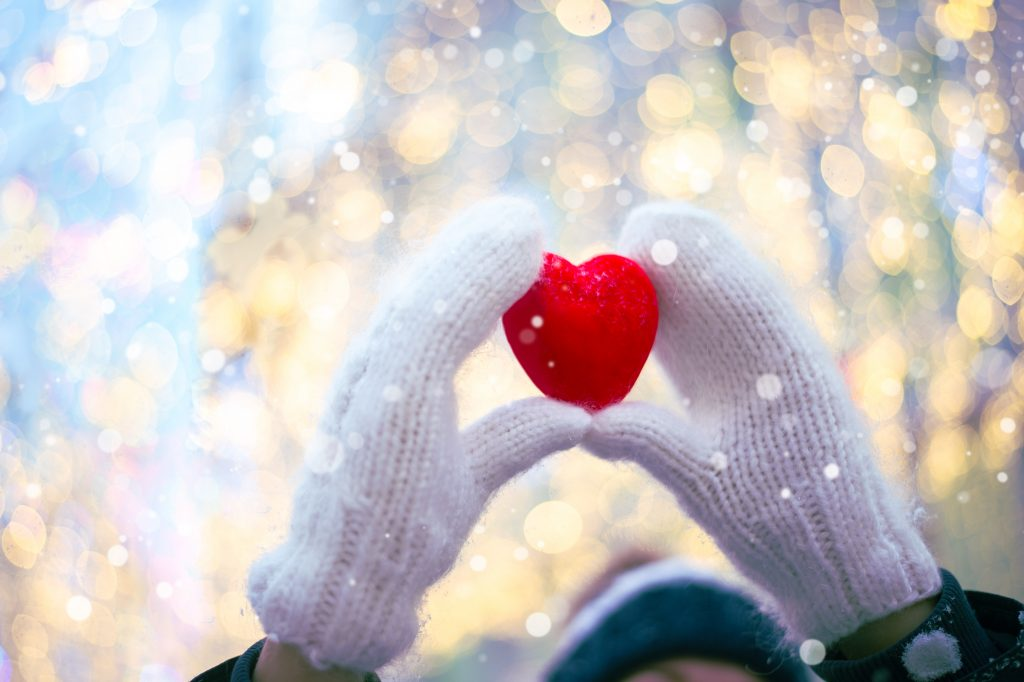 Woman hands in white knitted mittens with a red heart on a snow background with bokeh.