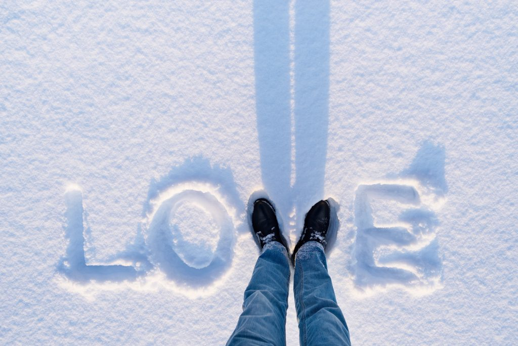 Love written in snow with the person who wrote it using their feet as the V.